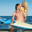 Young couple at the beach with surfboard. — Stock Photo