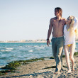 Romantic couple at the beach walking together. — Stock Photo