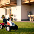 Tractor toy in front of mountain house. Dolomites, Italy. — Stock Photo #14580891
