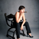 Woman smoking cigar sit on an old black chair. Studio fashion photo with grunge dark background. — Stock Photo