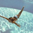 Underwater woman portrait with white bikini in swimming pool. — Stock Photo