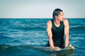 Surf młody człowiek w wodzie z deski surfingowej. — Zdjęcie stockowe