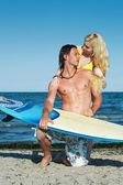 Jovem casal na praia com uma prancha de surf. — Fotografia Stock