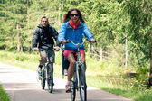 :Couple outdoors on bike. Bicycle path from St. Candid in italy — Stockfoto