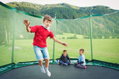 Young kids jumping in mountain scenery. — Stock Photo