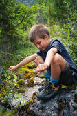 Portrait of six year old boy playing outdoors in the mountains. — Stock Photo