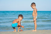 Two brothers playing on the beach. — Stock Photo