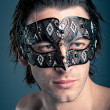 Close up portrait of young man with carnival mask against dark background — Stock Photo #14633147