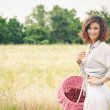 Young beautiful woman in a wheat field with basket of cherries — Stock Photo #14633303