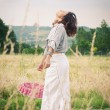 Young beautiful woman in a wheat field with basket of cherries — Stock Photo #14633315