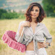 Young beautiful woman in a wheat field with basket of cherries — Stock Photo #14633323