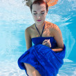 Underwater woman portrait with blue dress in swimming pool - Stock Photo