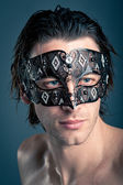 Close up portrait of young man with carnival mask against dark background — Stock Photo