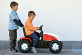 Two brothers playing with tractor toy outdoors — Stock Photo