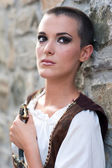 Beautiful girl wearing a medieval dress. Stone wall background — Stock Photo