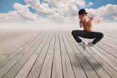Young man acrobatic jump over on a wood floor and a cloudy blue — Stock Photo
