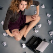 Oung desperate girl writing with an old typewriter and blank sheets of paper — ストック写真