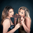 Two smiling attractive girlfriends eating chocolate bar, blond and brunette — Stock Photo #14756585