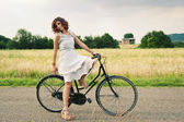 Pretty young woman relaxing with bike in a country road — Stok fotoğraf