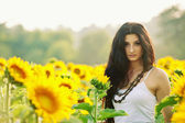 Young beautiful woman in a sunflower field with white dress — Stock Photo
