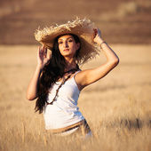 Young sexy woman in a wheat field with white dress and straw hat — Stock Photo
