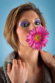 Portrait of beautiful girl with gerbera flower in her mouth against blue background — Stock Photo