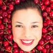 Young woman smiling face portrait surrounded by cherries — Stock Photo