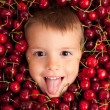 Kid smiling face portrait surrounded by cherries — Stock Photo #14830853
