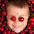 Kid smiling face portrait surrounded by cherries — Stock Photo