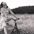 Beautiful black and white image of young woman riding bike in a country road — Stock Photo