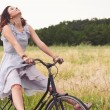 Pretty young woman riding bike in a country road — Stock Photo #14830915