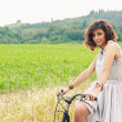 Beautiful young woman portrait with bike in a country road — Stock Photo #14830917