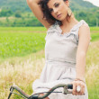Beautiful young woman portrait with bike in a country road — Stock Photo #14830919