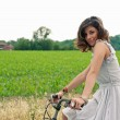 Beautiful young woman portrait with bike in a country road — Stock Photo #14830921