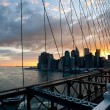 Panoramic shot of Manhattan skyline and Liberty island from the Brooklyn bridge — Stock Photo