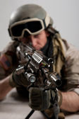 Soldier with rifle against white background. Shallow depth of field — Stock Photo