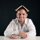 Young man playing with a book as a hat against black background — Stock Photo