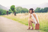 Beautiful girl waiting on a country road with her suitcase — Stock Photo