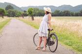 Hübsche junge frau entspannend mit fahrrad in einer landstraße — Stockfoto