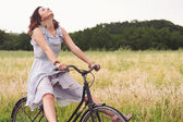 Pretty young woman riding bike in a country road — Stok fotoğraf