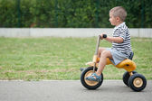 Four year old kid playing outdoor on tricycle — Stock Photo