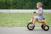 čtyři roky starý kluk hraje venkovní na tříkolka — Stock fotografie