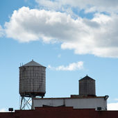 Water towers on a roof of a building in New York City — Stock Photo
