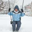 Stock Photo: Kid swinging in snow