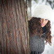 Portrait of beautiful girl in the snow hiding behind a tree - Stock Photo