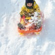Kid sliding with bob in the snow — Stock Photo