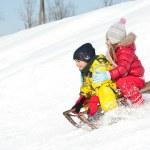 zwei Kinder schieben mit Schlittenfahren im Schnee — Stockfoto