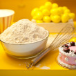Baking ingredients with eggbeater and cake on a yellow kitchen background — Stock Photo