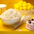 Baking ingredients with eggbeater and cake on a yellow kitchen background - Stock Photo