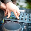 Young man working as dj with mixer. Shallow focus on hands - Stock Photo